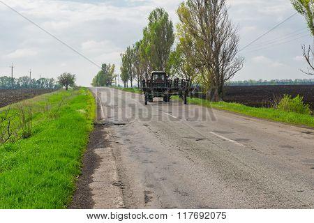 Farmer's tractor transporting harrows on nearest field at spring season