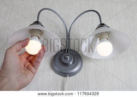 Hand Twists Led Lightbulb In A Lamp On White Wall
