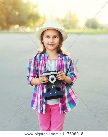 Portrait Of Little Girl Child Photographer With Retro Camera In City