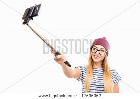 Happy Girl In Cap And Glasses Making Photo By Selfie Stick
