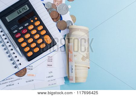 Mortgage And Utility Bills, Coins And Roll Of Banknotes, Calculator, Copy Space