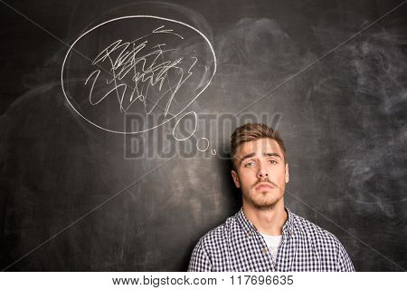 Young Man Against The Background Of Chalkboard Solving A Problem