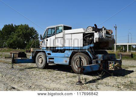 The disassembled loader crane. Old machinery repair.