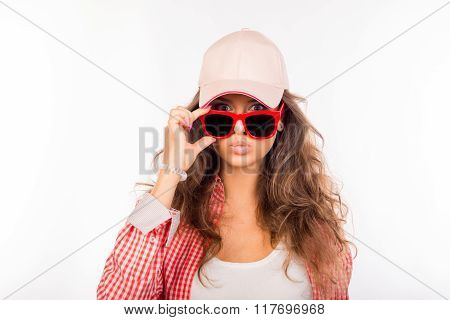 Young Serious Girl In Pink Hat Touching Her Glasses And Pouting