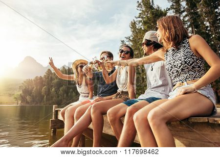 Young Friends Sitting On A Pier Toasting Beers