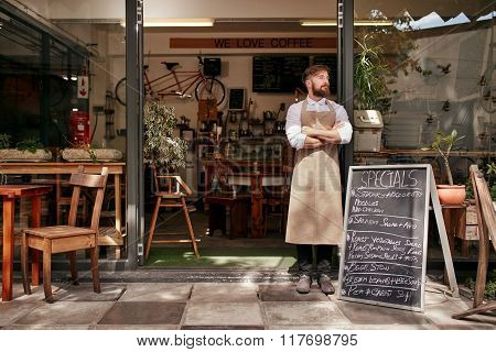 Young Man Standing At The Entrance Of His Coffee Shop