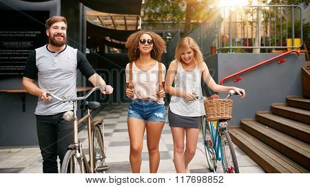 Three Young Friends Walking In The City With Bicycles