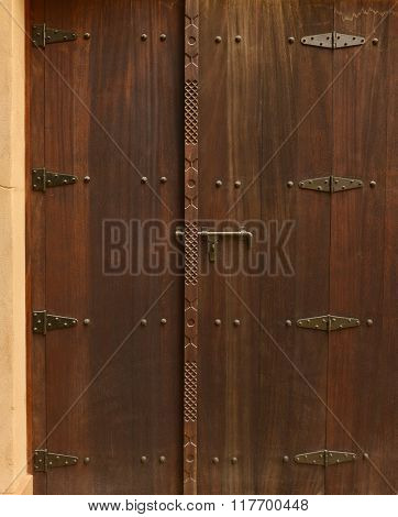 Solid traditional wooden door panel with many hinges.