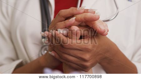Close Up Of Doctor's Hands Holding Patient's Hand
