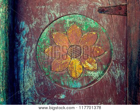 Closeup of carved floral design pattern on weathered wooden door.