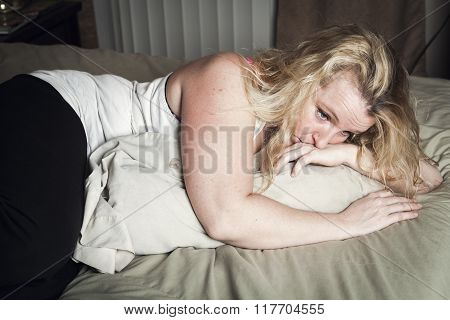 A woman feel sick lying down on bed