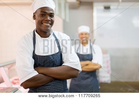 portrait of smiling african american butcher with colleague on background