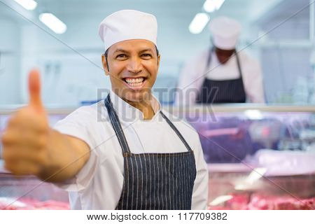 cheerful male butcher thumb up in butchery