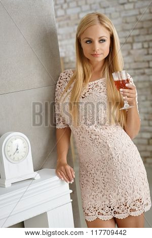 Pretty blonde woman in mini dress holding a glass of wine, leaning against wall.