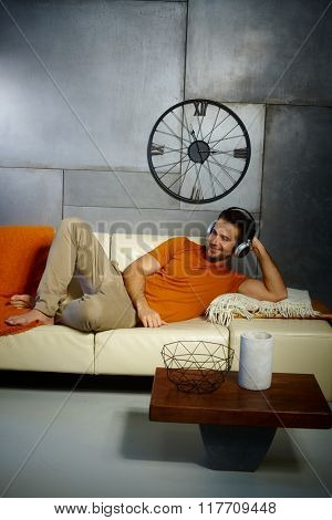 Young man lying on sofa, listening to music through headphones, smiling.