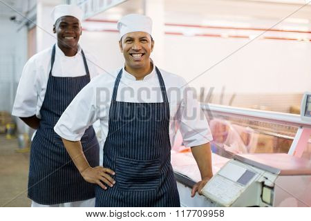 portrait of happy butchery workers standing next to scale