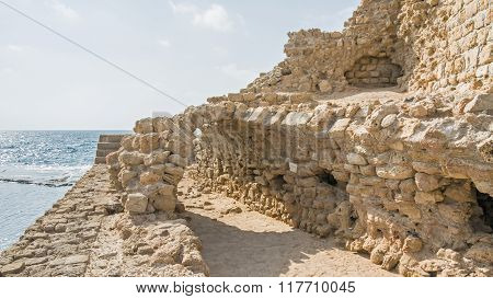 Remains of ancient harbor embankment against Mediterranean Sea background