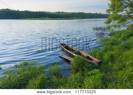View on river with wooden boat laid up near gangway on riverbank
