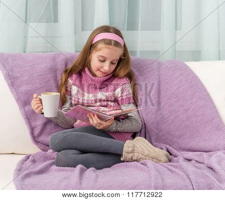 little cute girl on sofa with warm blanket and cup watching a magazine
