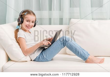 smiling little girl listening something with headphones and note book on sofa looks at camera