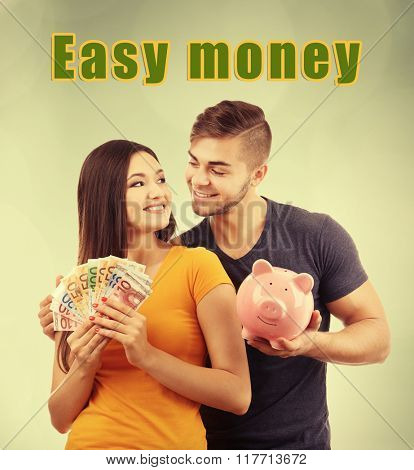 Couple piggy bank and banknotes on green background