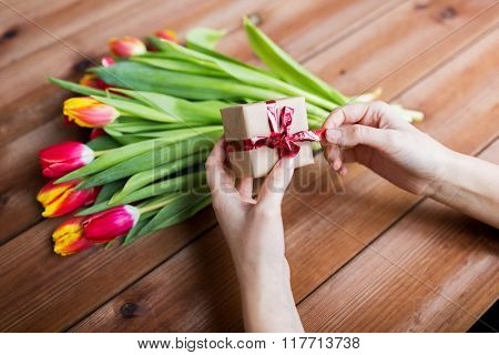 peoople, holidays and greeting concept - close up of woman holding gift box and tulip flowers
