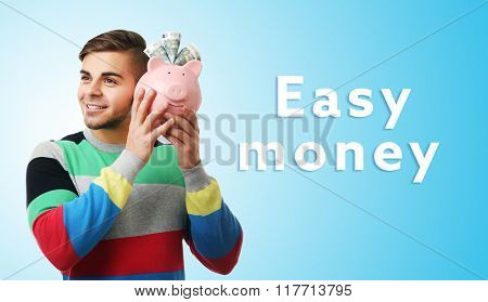 Man with money box and banknotes on blue background