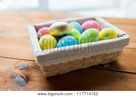 easter, holidays, tradition and object concept - close up of colored easter eggs in wicker basket