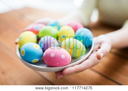 easter, holidays, tradition and people concept - close up of woman hands holding colored easter eggs on plate