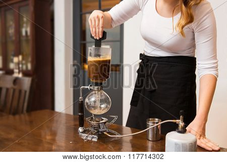 equipment, coffee shop, people and technology concept - close up of woman stirring coffee grounds in siphon coffeemaker top vessel at cafe bar or restaurant kitchen