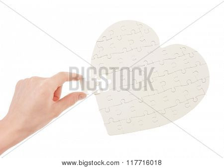 Incomplete jigsaw puzzle in a shape of a heart isolated on white