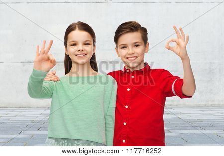 childhood, friendship, gesture and people concept - happy smiling boy and girl hugging and showing ok hand sign over urban street background