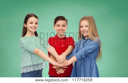 childhood, education, school, friendship and people concept - happy smiling children with hands on top over green chalk board background