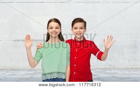 childhood, friendship, gesture and people concept - happy smiling boy and girl hugging and waving hand over urban street background