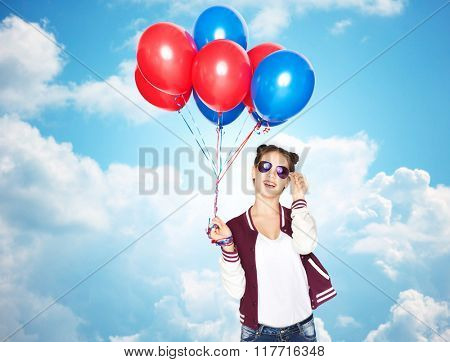 people, teens, holidays, party and summer concept - happy smiling pretty teenage girl in sunglasses with helium balloons over blue sky and clouds background