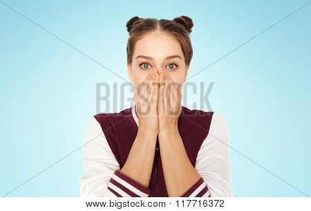 people, emotion, expression and teens concept - scared or confused teenage girl over blue background