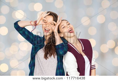 people, friends, teens and friendship concept - happy smiling pretty teenage girls having fun and making faces over holidays lights background