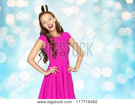 people, holidays and fashion concept - happy young woman or teen girl in pink dress and princess crown over blue holidays lights background