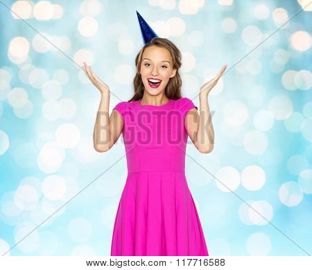 people, holidays, emotion, expression and celebration concept - happy young woman or teen girl in pink dress and party cap over blue holidays lights background