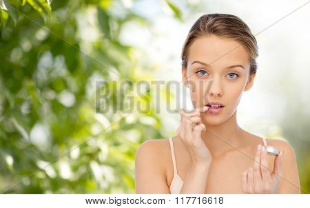 beauty, people and lip care concept - young woman applying lip balm to her lips over green natural background