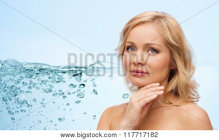 beauty, moisturizing, people and skincare concept - smiling woman with bare shoulders touching face over blue background and water splash