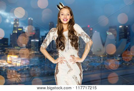 people, holidays, night life and celebration concept - happy young woman or teen girl in party dress and princess crown