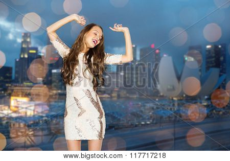 people, night life, holidays and fashion concept - happy young woman or teen girl in fancy dress with sequins and long wavy hair dancing at party