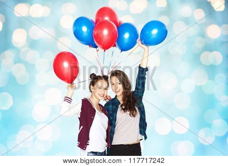 people, friends, teens, holidays and party concept - happy smiling pretty teenage girls with helium balloons over blue holidays lights background