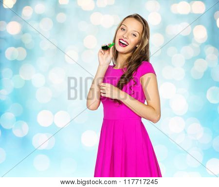 people, holidays and celebration concept - happy young woman or teen girl in pink dress and party cap over blue holidays lights background