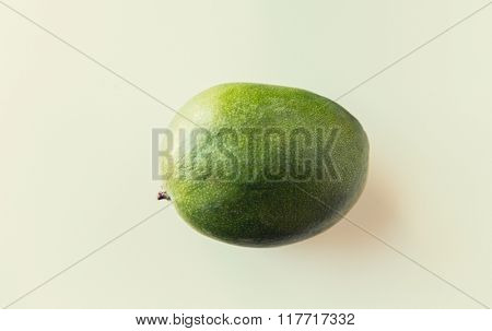 fruits, diet, eco food and objects concept - ripe green mango over white
