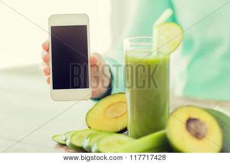 healthy eating, technology, diet and people concept - close up of woman hands with smartphone, green fresh juice and vegetables sitting at table