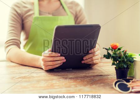 people, gardening, flowers and profession concept - close up of woman or gardener holding tablet pc computer at home
