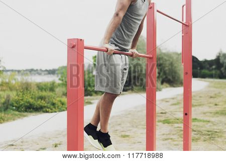fitness, sport, exercising, training and lifestyle concept - close up of young man doing pull ups on horizontal bar outdoors