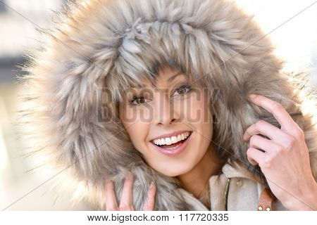 Portrait of beautiful woman with winter coat and fur hood